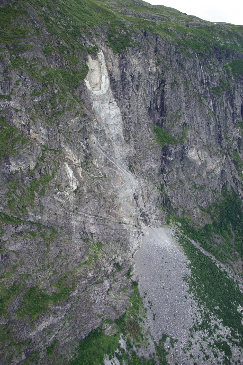 Figure 2: Example of a rockslide that occurred in 1992, by Jimdalen, near Tafjorden. A large block fell (notice the light area) from the extremely steep cliff and formed a large talus deposig along the foot of the cliff. (Photo: Aline Saintot, NGU).