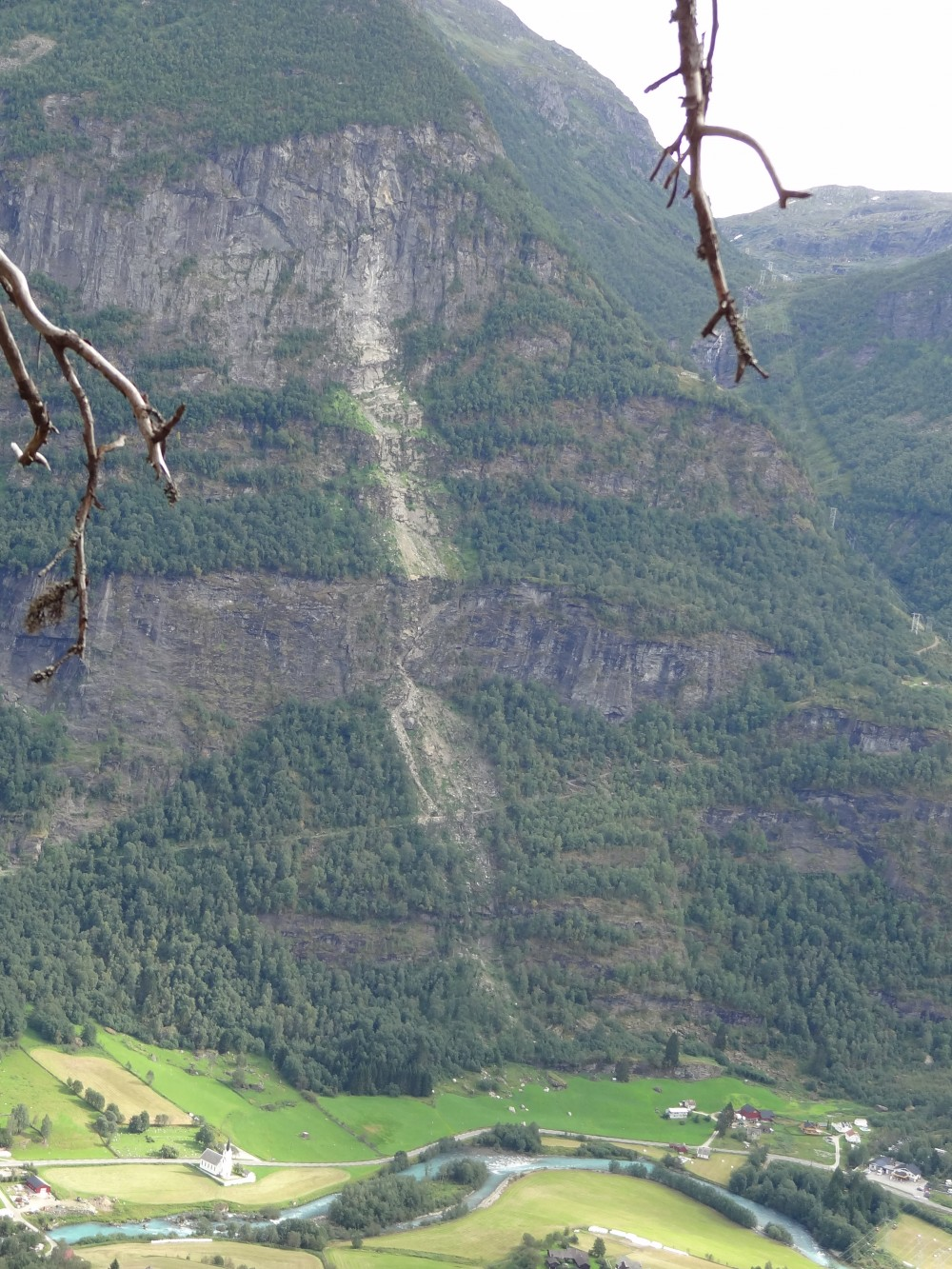 Figure 3: Rockfall in Fortundalen (Sogn og Fjordane) from 2014, with obvious source area in the uppermost part of the cliff. Along the mountainside we can see fresh tracks of the landslide where the vegetation has been destroyed. Blocks from the even are scattered on the field and stopped just short of the road. (Photo: Freddy Yugsi Molina, NGU).