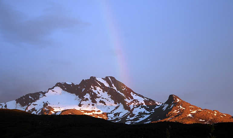 A soft sloped mountain, partially covered with snow with a dark blue sky and rainbow in the background.