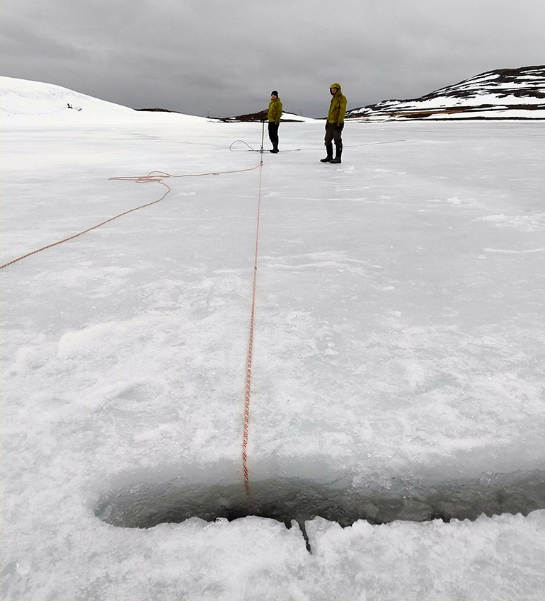 Two researchers from NGU in yellow jackets are standing by a hole in the ice. A rope goes down into the icy water.